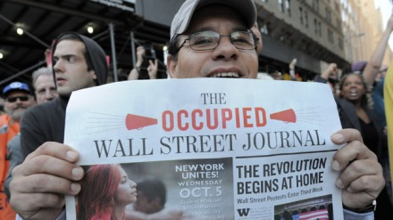 "A man holds up a copy of the ""Occupied W"